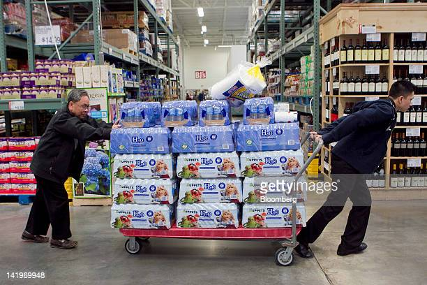Customers move a cart full of water through a BJ's Wholesale Club Inc store in Falls Church Virginia US on Tuesday March 27 2012 The US Bureau of...