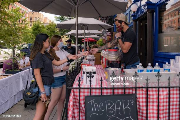 Customers order a drinks to-go outside a restaurant as the city reopens from the coronavirus lockdown on June 15, 2020 in Hoboken, New Jersey. The...
