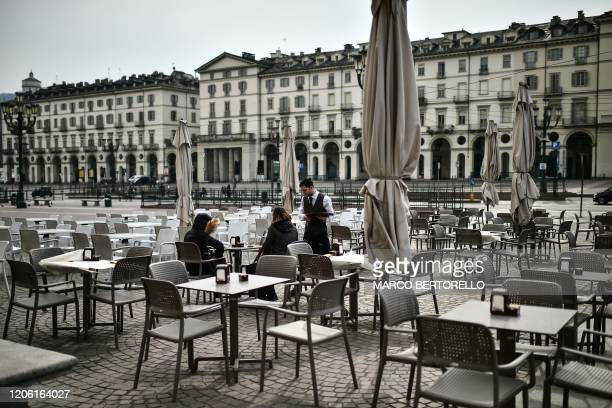 Customers order drinks at a deserted cafe terrace on March 9, 2020 on Piazza Vittorio in Turin, as Italy is battling the world's second-most deadly...