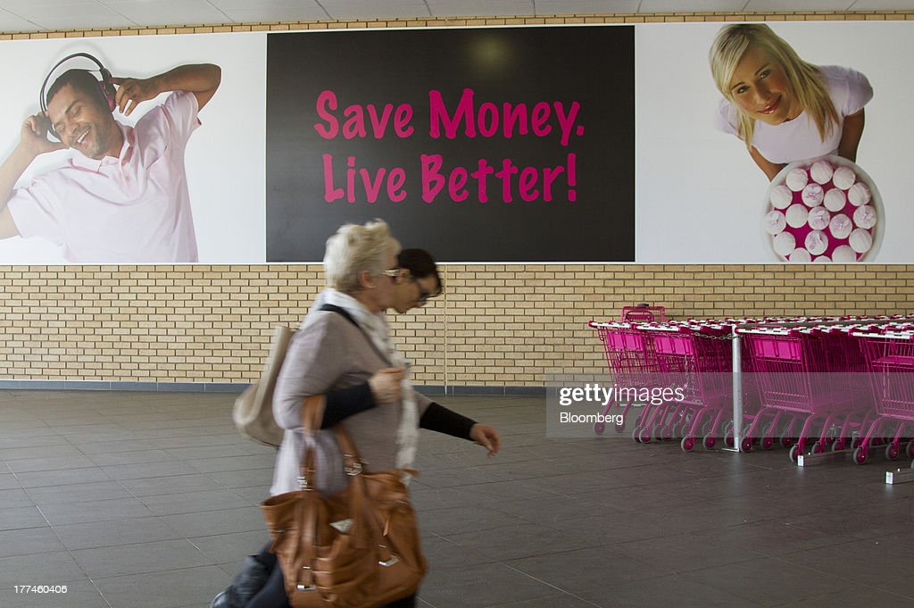 Customers pass an advertisement to 'Save Money, Live Better' beside parked shopping carts outside a Game supermarket, part of Massmart Holdings Ltd., in the Fourways district of Johannesburg, South Africa, on Thursday, Aug. 22, 2013. Massmart Holdings Ltd., the South African food and goods wholesaler owned by Wal-Mart Stores Inc., said revenue growth continued to slow in August after a downturn in consumer spending hurt first-half earnings. Photographer: Nadine Hutton/Bloomberg via Getty Images
