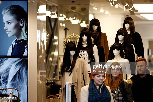 Customers pass mannequins displaying women's clothes as they exit a New Look fashion store operated by New Look Group Ltd on Oxford Street in London...