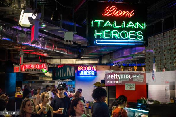 Customers pass under a neon sign for Lioni Heroes inside DeKalb Market Hall at City Point in the Brooklyn borough of New York US on Tuesday July 18...