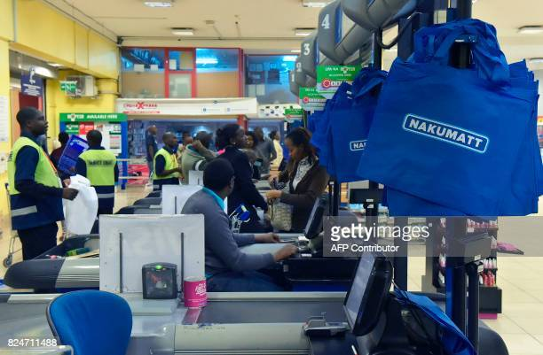 Customers pay at the register in a Nakumatt supermarket in Nairobi on July 22 2017 Once a Kenyan success story homegrown Nakumatt supermarkets are...