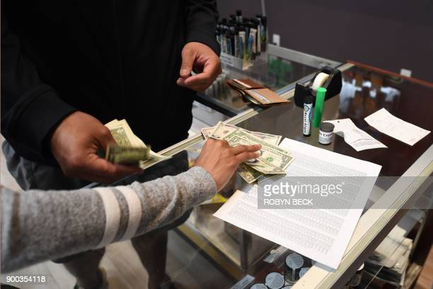 Customers pay cash for their purchase at the Green Pearl Organics dispensary on the first day of legal recreational marijuana sales in California...