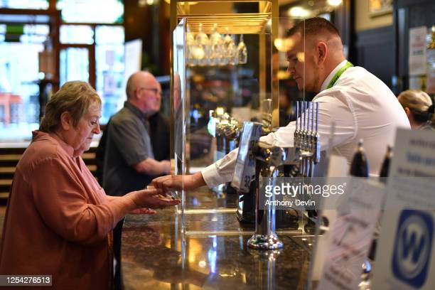 Customers pay for drinks through a perspex screen at the Regal Moon JD Wetherspoons pub on July 04, 2020 in Rochdale, England. The UK Government...
