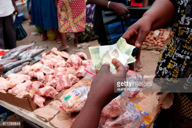 Customers pay for goods at a market on January 19 2018 in Luanda Angola Angolan President Joao Lourenco was elected five months ago promising an...