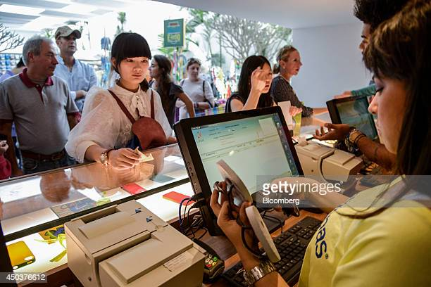 Customers pay for Havaiana flip flops at an Alpargatas SA Havaianas store in Sao Paulo Brazil on Saturday June 7 2014 Sao Paulobased Alpargatas SA...