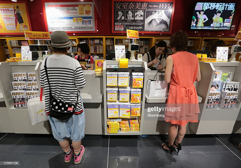 Customers pay for their purchases at cashier counters at a Tower Records Japan Inc. store in Tokyo, Japan, on Monday, July 1, 2013. Music sales in the country rose for the first time in five years, led by tunes delivered on CDs and other physical media, bucking the trend in developed markets as cheaper downloads gain ground. Physical media made up 82 percent of Japanese music sales last year, versus 37 percent in the U.S., said the Recording Industry Association of Japan. Photographer: Yuriko Nakao/Bloomberg via Getty Images