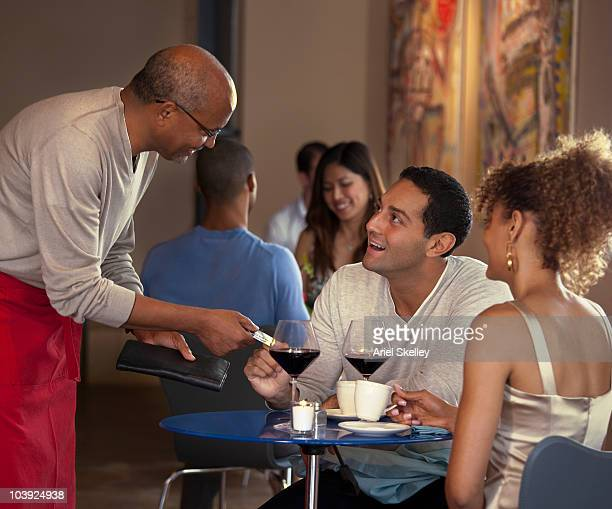 Customers paying waiter at restaurant