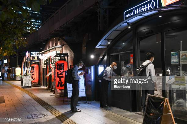 Customers pick up food from a restaurant built under railway tracks in Tokyo, Japan, on Tuesday, Sept. 8, 2020. In Tokyo, the spaces beneath elevated...