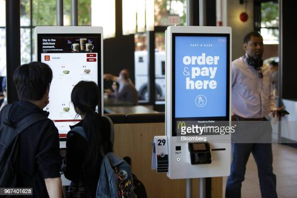 Customers place an order on a kiosk at the restaurant inside the new McDonald's Corp headquarters in Chicago Illinois US on Monday June 4 2018...