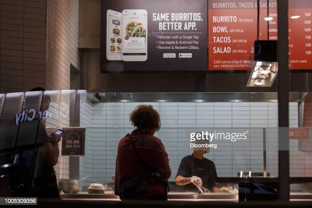 Customers place orders beneath an advertisement for the Chipotle Mexican Grill Inc mobile app inside the company's restaurant in Culver City...