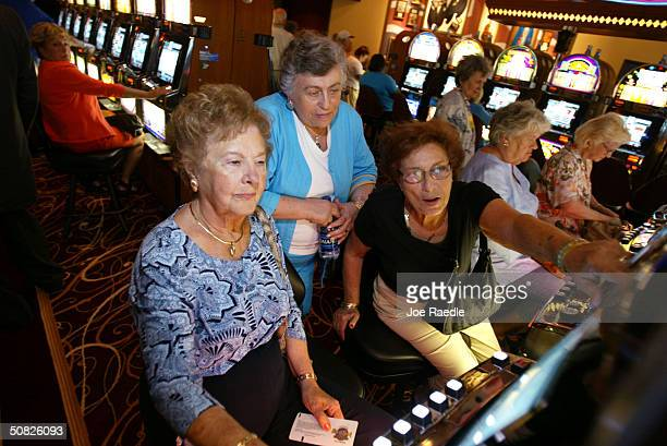 Customers play a slot machine May 11 2004 during the grand opening for the Seminole Hard Rock Hotel and Casino in Hollywood Florida South Florida's...