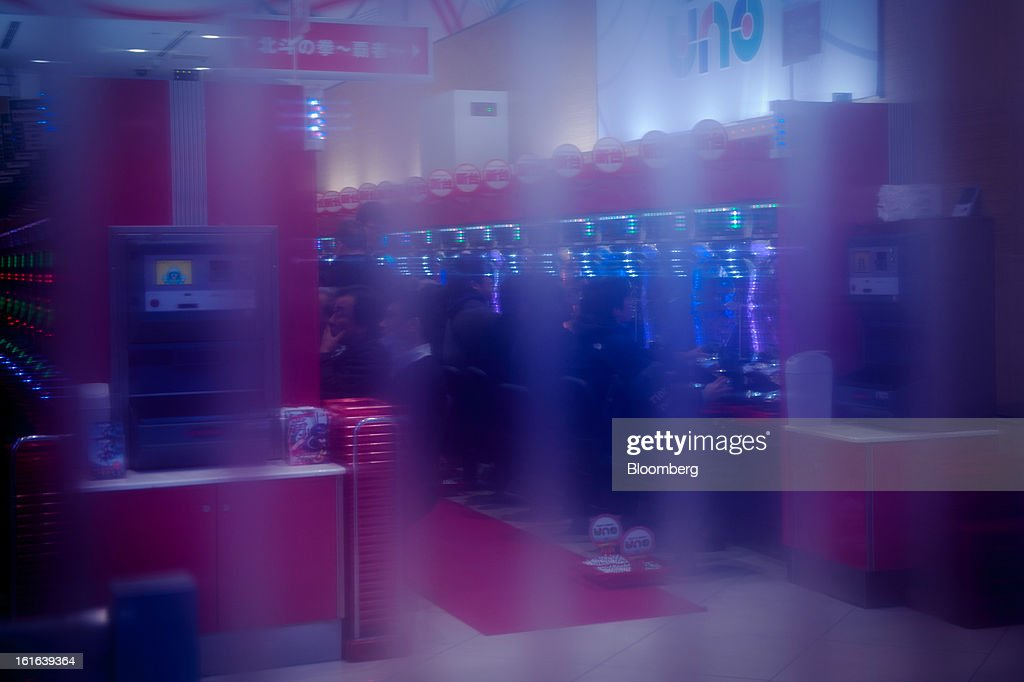 Customers play inside a pachinko parlor, viewed through a plastic screen in the district of Ginza in Tokyo, Japan, on Wednesday, Feb. 13, 2013. Japan's economy unexpectedly shrank last quarter as falling exports and a business investment slump outweighed improved consumption, highlighting the challenge facing Prime Minister Shinzo Abe as he seeks to end deflation. Photographer: Noriko Hayashi/Bloomberg via Getty Images