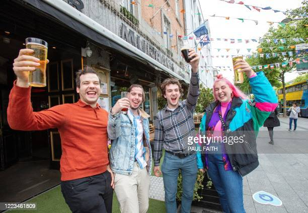 Customers pose for a photograph with their drinks outside the re-opened Murray's Bar in Dublin on June 29 as lockdown measures begin to be eased. -...