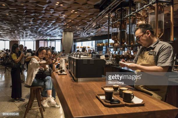 Customers pose for a selfie photograph as coffee beverages are served on a counter inside the Starbucks Corp Reserve Roastery store in Shanghai China...