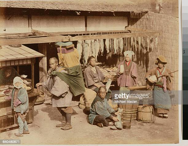 Customers, proprietors, and a samisen player at a fish market in Japan, ca. 1890s.