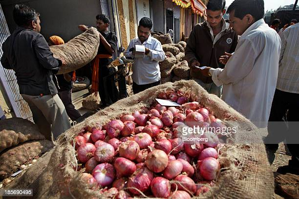 Customers purchase bags of onions from a wholesale market in Nashik Maharashtra India on Wednesday Oct 23 2013 Onion prices in India may extend a...