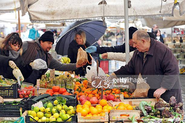 Customers purchase produce from a fruit and vegetable market stall at the Campo dei Fiori market in Rome Italy on Monday Dec 10 2012 The imminent end...