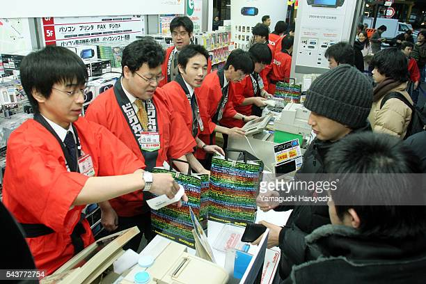 Customers purchase Sony Corp's new PlayStation Portable video game console on the morning of its Japan debut at an electronics shop