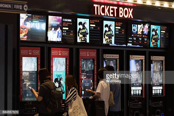 Customers purchase tickets at a selfserving machine at the CJ CGV Co Yeouido branch movie theater in Seoul South Korea on Wednesday May 25 2016 CJ...