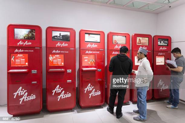 Customers purchase tickets using AirAsia Bhd automated sales kiosks at Kuala Lumpur International Airport 2 in Sepang Selangor Malaysia on Thursday...