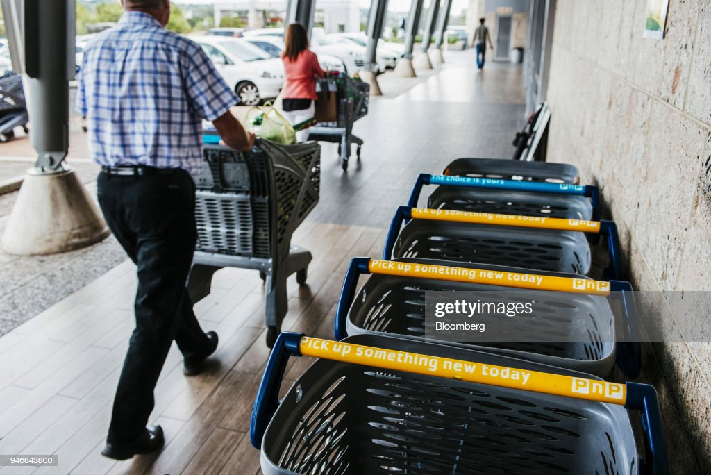 Customers push branded shopping carts as they depart a Pick n Pay Stores Ltd. supermarket in Johannesburg, South Africa, on Monday, April 9, 2018. As trade tensions and the Syrian conflict roiled markets this month, South Africas rand has been stuck in an unusually narrow range for one of the worlds most volatile currencies. Photographer: Waldo Swiegers/Bloomberg via Getty Images