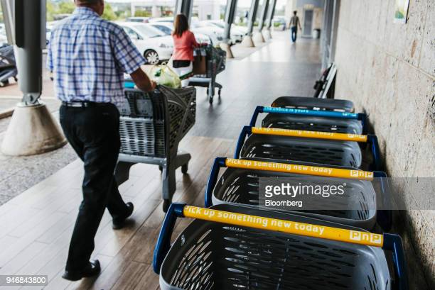 Customers push branded shopping carts as they depart a Pick n Pay Stores Ltd supermarket in Johannesburg South Africa on Monday April 9 2018 As trade...