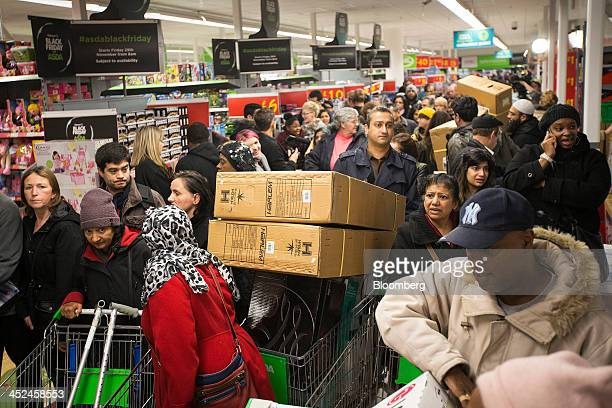 Customers push loaded shopping carts through crowded aisles as they look for bargains during a Black Friday discount sale inside an Asda supermarket...