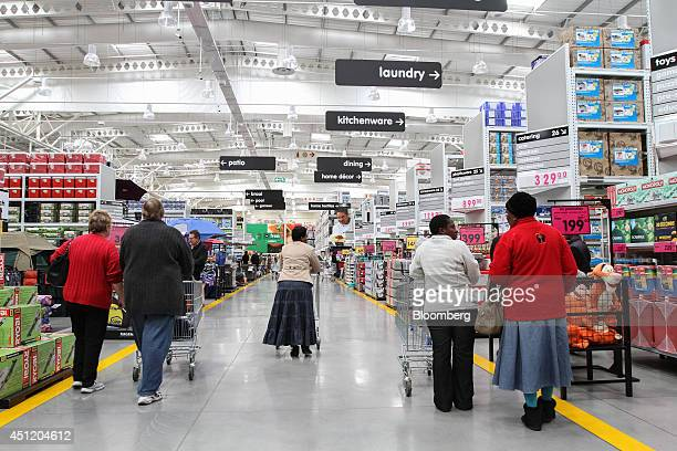 Customers push shopping carts along an aisle past homewares inside a Makro cash and carry store operated by Massmart Holdings Ltd in Alberton South...