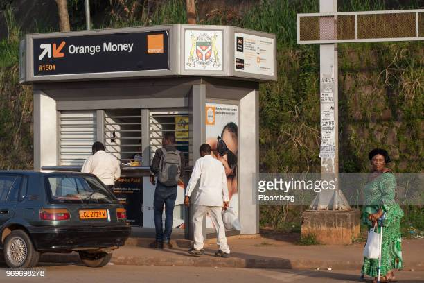 Customers queue at an Orange Money Ltd moneytransfer kiosk at Nlongkak roundabout in Yaounde Cameroon on Tuesday June 5 2018 Cameroon adjusted its...