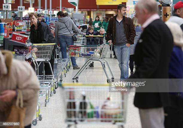 Customers queue at the checkout counters inside a Morrisons supermarket operated by William Morrisons Supermarkets Plc in Crawley UK on Tuesday March...