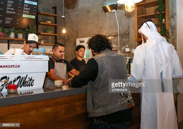Customers queue for their orders at the 'Flat White' cafe in the Qatari capital Doha's Tawar Mall on June 8 2018 Tawar Mall looks like any of Qatar's...