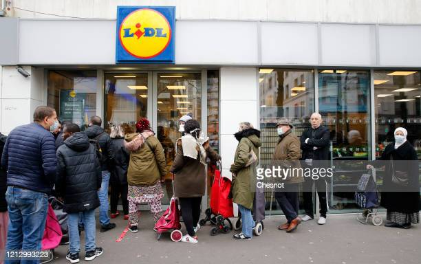 Customers queue in front of a Lidl supermarket the day after the announcement by French President Emmanuel Macron of the confinement of the French...