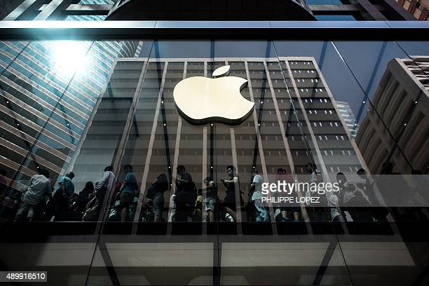 Customers queue inside an Apple store in Hong Kong on September 25 2015 Apple was urged to act as rights campaigners said a Chinese touchscreen glass...