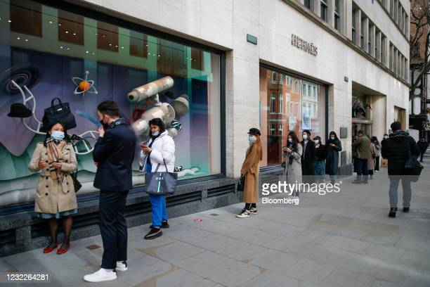 Customers queue outside a Hermes International SA luxury goods store in London, U.K., on Monday, April 12, 2021. Non-essential retailers as well as...