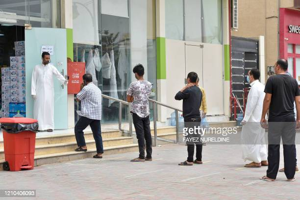 Customers queue outside a supermarket while maintaining social distancing during a nationwide curfew to stem the spread of COVID19 in the Saudi...