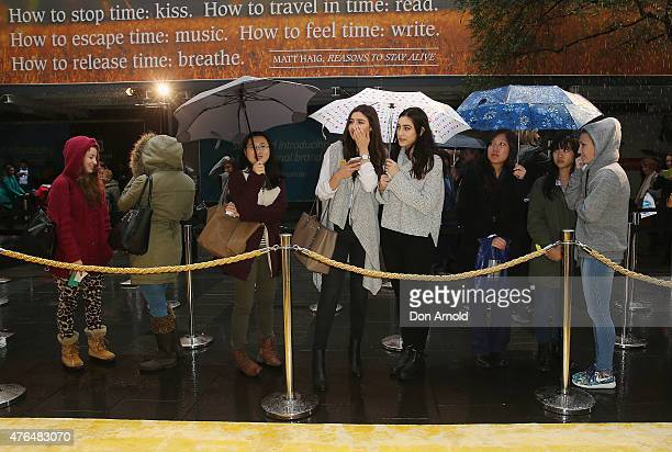 Customers queue outside in the rain at the opening of the 'FOREVER 21' flagship store on Pitt Street on June 10, 2015 in Sydney, Australia.