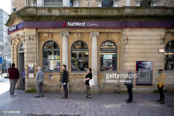 Customers queue outside Natwest bank, practising social distancing, on March 24, 2020 in Cardiff, United Kingdom. British Prime Minister, Boris...