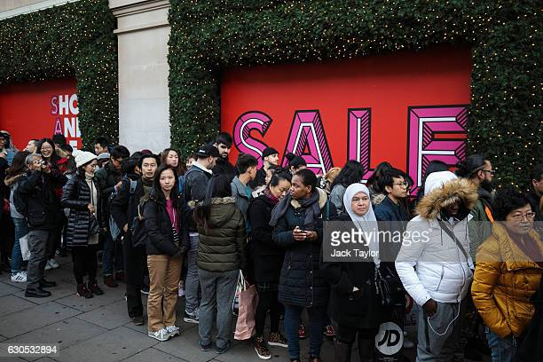 Customers queue outside Selfridges on Oxford Street before the department store opens for its Boxing Day sale on December 26 2016 in London England...