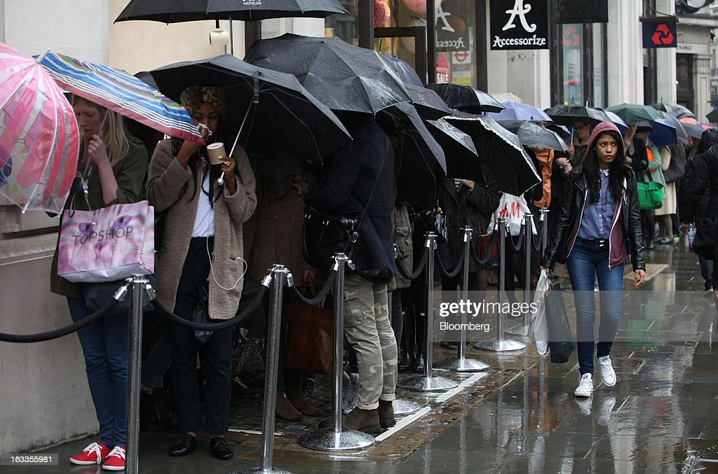 Customers queue outside the new '& Other Stories' store operated by Hennes & Mauritz AB (H&M) on the launch day in London, U.K., on Friday, March 8, 2013. The Swedish retailer is diversifying with a sixth brand after falling behind larger competitor Inditex SA in the race for the price-sensitive fashionista's euro. Photographer: Chris Ratcliffe/Bloomberg via Getty Images