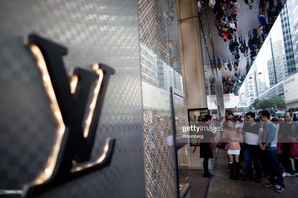 Customers queue to enter a Louis Vuitton store, operated by LVMH Moet Hennessy Louis Vuitton SA, in the Tsim Sha Tsui area of Hong Kong, China, on Saturday, Dec. 22, 2012. Hong Kong's economy is set for its weakest annual expansion since the global financial crisis as the European sovereign debt crisis damps global trade. Photographer: Lam Yik Fei/Bloomberg via Getty Images