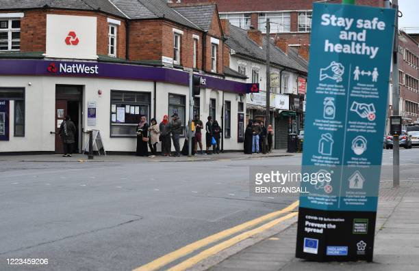 """Customers queue to enter a NatWest bank opposite a sign telling local residents how to """"Stay safe and Healthy"""" and advising on how to help """"Prevent..."""