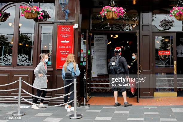 Customers queue to enter the Wetherspoon pub, Goldengrove in Stratford in east London on July 4 as restrictions are further eased during the novel...