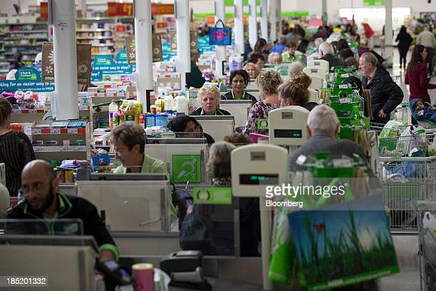 Customers queue to pay for their goods at checkout desks inside an Asda supermarket the UK retail arm of WalMart Stores Inc in Watford UK on Thursday...