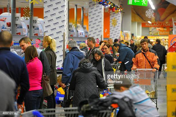 Customers queue to pay for their goods at the checkout desks inside a Tempo supermarket operated by Delhaize Group SA in Belgrade Serbia on Saturday...