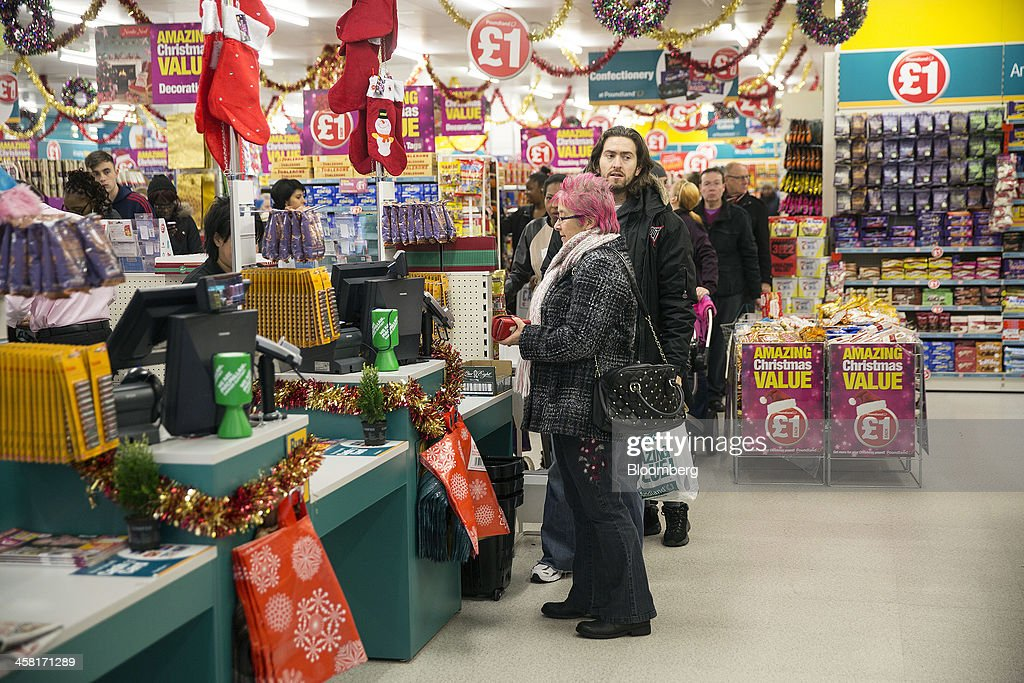 Customers queue to pay for their purchases at a check-out desk inside a Poundland discount store, operated by Poundland Holdings Ltd., in Birmingham, U.K., on Friday, Dec. 20, 2013. U.K. discount retailer Poundland has hired Rothschild to manage its IPO, according to the Sunday Times newspaper. Photographer: Simon Dawson/Bloomberg via Getty Images