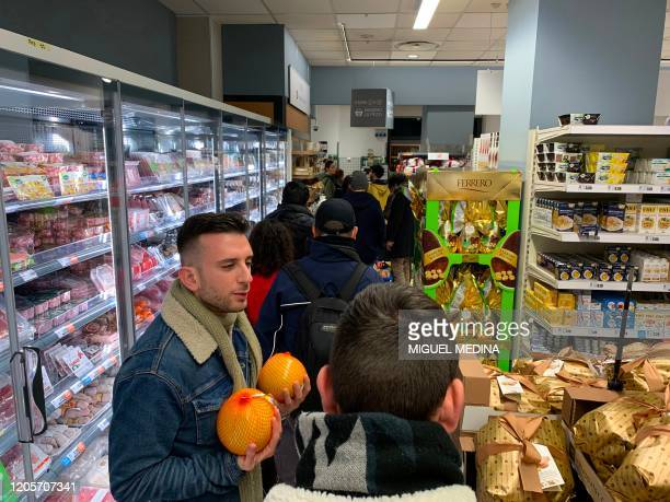 Customers queue to pay their food and essential products in a supermarket of Milan centre on late March 7 2020 after Italy prepared to quarantine...