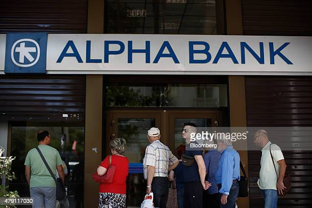 Customers queue to use an automated teller machine and wait to enter an open branch of the Alpha Bank AE bank in Athens Greece on Wednesday July 1...