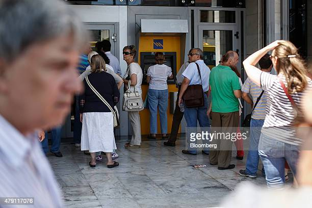 Customers queue to use an automated teller machine and wait to enter an open branch of the Piraeus Bank SA in Athens Greece on Wednesday July 1 2015...